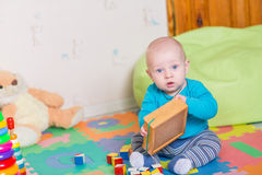 Cute little baby playing with colorful toys Stock Images