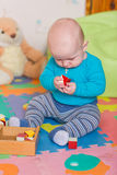 Cute little baby playing with colorful toys Royalty Free Stock Photos