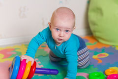 Cute little baby playing with colorful toys Royalty Free Stock Images