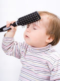 Cute little baby playing with a hairbrush Royalty Free Stock Photo