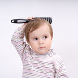 Cute little baby playing with a hairbrush Stock Images