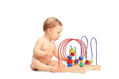 Cute little baby playing with a toy seated on the floor Royalty Free Stock Photos