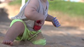 Cute little baby plays on the beach with paddle, rake and sand. stock video
