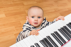 Cute little baby plays piano. At home Stock Photography