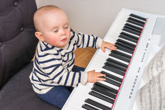 Cute little baby plays piano. At home Royalty Free Stock Image