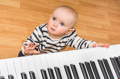 Cute little baby plays piano. At home Royalty Free Stock Images
