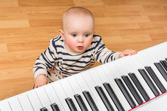 Cute little baby plays piano. At home Royalty Free Stock Photos