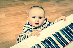 Cute little baby plays piano - retro style. Cute little baby plays piano at home - retro style Royalty Free Stock Images