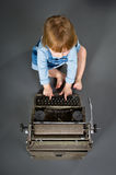 Cute little baby with retro style typewriter typing Royalty Free Stock Photo