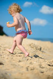 Cute little baby running at ocean beach Stock Image