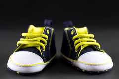 Cute little baby shoes. Yellow and dark blue cute baby shoes  on black Stock Images