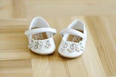 Cute little baby shoes on a floor. Cute little baby shoes on a wooden floor Royalty Free Stock Image