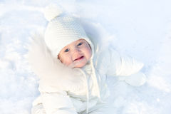 Cute little baby sitting in fresh winter snow. Cute little baby in a white jacket and white hat sitting in fresh winter snow Stock Image