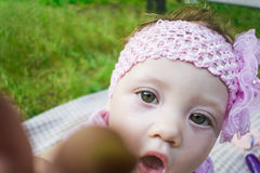 A cute little baby is sitting on the grass outside in the park. Newborn girl in a beautiful park outdoors, lying on a blanket and looking at the camera Royalty Free Stock Images