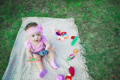 A cute little baby is sitting on the grass outside in the park. Portrait of a joyful young child outdoors in the park with toys Stock Image