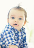 A cute little baby is sitting and looking into the camera Royalty Free Stock Image