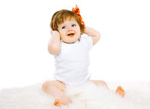 Cute little baby sitting playing and looking away Royalty Free Stock Images