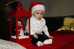 Cute little baby sitting by the window and looking away. Room decorated on Christmas. With santa`s hat royalty free stock image