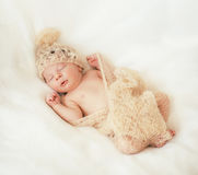 Little baby is  sleeping in a gentle knitted blanket. Cute little baby is  sleeping in a gentle knitted blanket of cream color Royalty Free Stock Photo