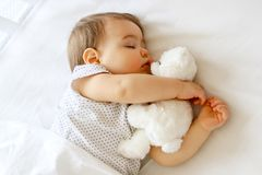 Cute little baby sleeping hugging his white teddy bear. Cute little baby sleeping hugging his small white teddy bear, best friends. Child sleeping schedule stock images
