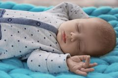 Cute little baby sleeping on plaid at home,. Closeup Stock Images