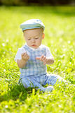 Cute little baby in summer  park on the grass. Sweet baby outdoo Royalty Free Stock Images
