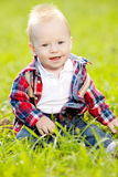 Cute little baby in summer  park on the grass. Sweet baby outdoo Royalty Free Stock Photo