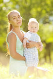 Cute little baby in summer  park with mother  on the grass. Swee Royalty Free Stock Image
