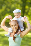 Cute little baby in summer park with mother on the grass. Swee. Cute little baby in the park with mother on the grass. Sweet baby and mom outdoors. Smiling stock image