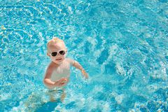 Cute little baby with sunglasses splashing happily in the pool with clear blue water. Cute little baby with sunglasses splashing happily in the pool with clear Stock Image
