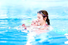 Cute little baby in swimming pool with his mother royalty free stock photos