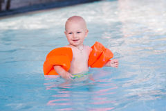 Cute little baby in swimming pool. Cute little baby learning how to swim in swimming pool royalty free stock photography