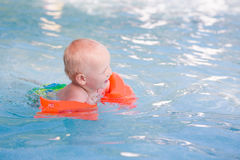 Cute little baby in swimming pool. Cute little baby learning how to swim in swimming pool royalty free stock photo