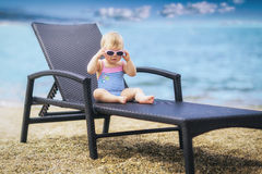 Cute little baby in swimsuit and wearing pink sunglasses. Royalty Free Stock Photo