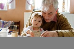 Cute little baby toddler girl and handsome senior grandfather painting with colorful pencils at home. Grandchild and man stock photography