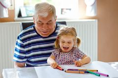 Cute little baby toddler girl and handsome senior grandfather painting with colorful pencils at home. Grandchild and man royalty free stock images