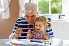Cute little baby toddler girl and handsome senior grandfather painting with colorful pencils at home. Grandchild and man royalty free stock photography