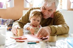 Cute little baby toddler girl and handsome senior grandfather painting with colorful pencils at home. Grandchild and man royalty free stock photo