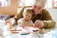 Cute little baby toddler girl and handsome senior grandfather painting with colorful pencils at home. Grandchild and man. Cute little baby toddler girl and stock photos