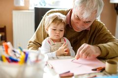 Cute little baby toddler girl and handsome senior grandfather painting with colorful pencils at home. Grandchild and man. Cute little baby toddler girl and stock images