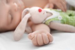 Cute little baby with toy sleeping on bed. At home Stock Photography