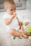 Cute little baby with toys sitting on carpet Stock Photography