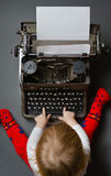 Cute little baby typing on typewriter Stock Image