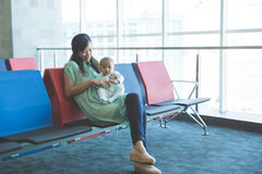 Cute little baby waiting in the airport with her mother Stock Image
