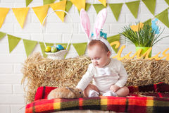 Cute little baby wearing bunny ears on Easter day and stroking r stock images