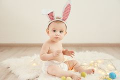 Cute little baby wearing bunny ears sitting on furry rug. With garland stock photos