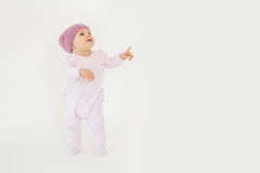 Cute little baby wearing hat standing on floor and pointing. Photo of cute little baby girl wearing hat standing on floor isolated over white background Stock Images