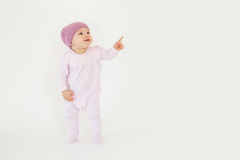 Cute little baby wearing hat standing on floor and pointing. Photo of cute little baby girl wearing hat standing on floor isolated over white background Stock Image