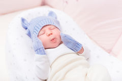 Cute little baby wearing knitted blue hat with ears and mittens. Lying in beautiful cradle with closed eyes and making funny face. Security and childcare stock photography