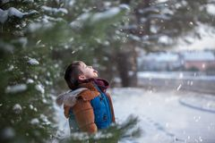Cute little baby who catches snowflakes mouth in winter sunny day. Little toddler boy playing with snow in winter. Cute little baby who catches snowflakes mouth stock photography